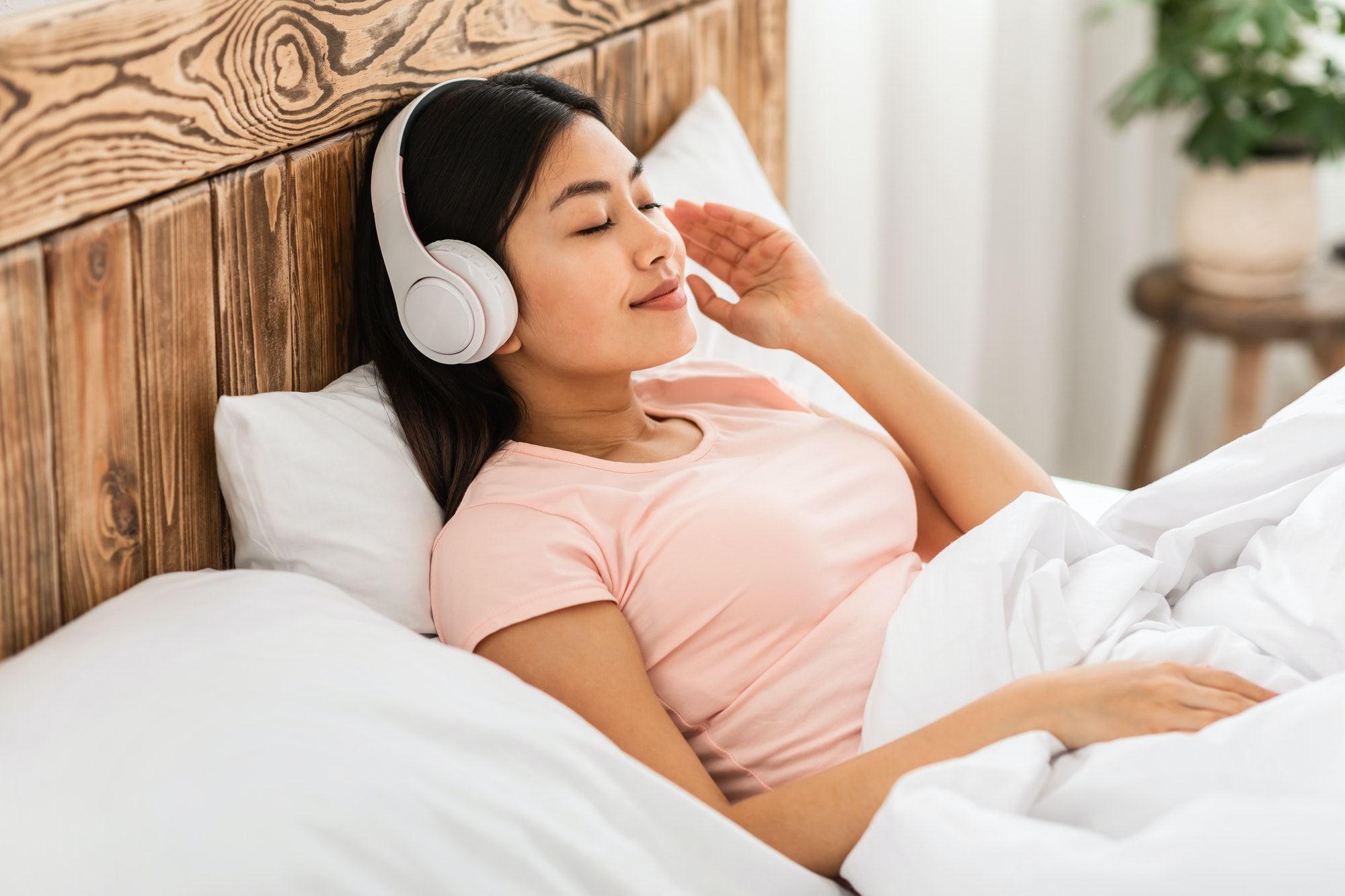 Chinese Girl In Earphones Listening To Podcast Lying In Bed